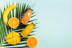 Naranja fresca, plátano, piña, smoothie del mango y frutas jugosas en hojas de palma sobre fondo azul Bebida del verano del Detox imagenes de archivo