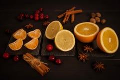 Naranja, limón, mandarín, en un fondo negro foto de archivo