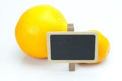 Naranja, mandarín y tarjeta aislados en blanco Fotografía de archivo