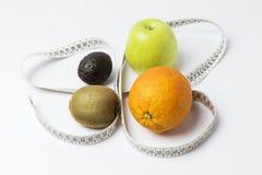 Naranja, manzana, kiwi y aguacate rodeados por una cinta métrica fotos de archivo
