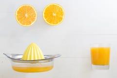 Naranja partida en dos con el vidrio y el exprimidor del zumo de naranja con el espacio en blanco Foto de archivo libre de regalías