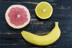 Naranja, pomelo y plátano en la tabla Foto de archivo
