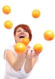 Naranja que hace juegos malabares de la muchacha Fotografía de archivo libre de regalías