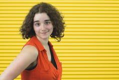 Naranja que lleva de la morenita fresca de la chica joven en fondo amarillo de la raya imagen de archivo