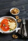 Naranja, queso y galletas en una placa blanca en una superficie de madera oscura Fotos de archivo