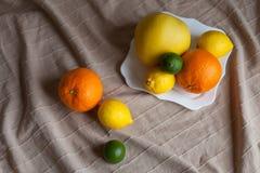 Naranja un limón una cal en una tabla Imágenes de archivo libres de regalías