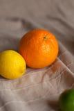 Naranja un limón una cal en una tabla Foto de archivo