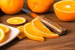 Naranja y cuchillo cortados en una tabla de madera Foto de archivo libre de regalías