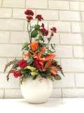 Naranja y flor en el florero blanco Imagen de archivo