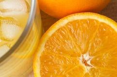 Naranja y jugo con el hielo de arriba Fotografía de archivo libre de regalías