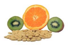 Naranja y kiwi con las píldoras de la vitamina Fotografía de archivo libre de regalías