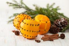 Naranjas adornadas con los clavos y los palillos de canela con los conos del pino Imagen de archivo
