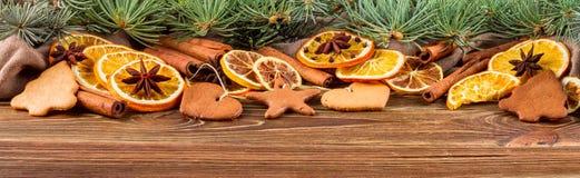 Naranjas, anís de estrella, palillos de canela y pan de jengibre secados en un fondo de madera -- Christmasbackground, bandera Fotografía de archivo