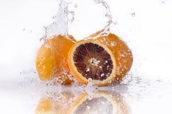 Naranjas con el chapoteo del agua Imagenes de archivo