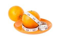 Naranjas con la cinta de la medida en la placa anaranjada Fotos de archivo libres de regalías