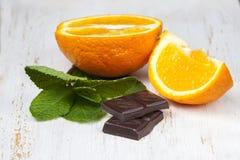 Naranjas con la menta fresca y el chocolate en una madera blanca del fondo Imágenes de archivo libres de regalías