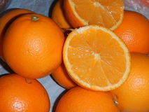 Naranjas con la una pieza del corte de la fruta Fotografía de archivo