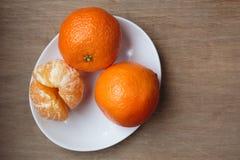 Naranjas de la clementina en la placa Imágenes de archivo libres de regalías