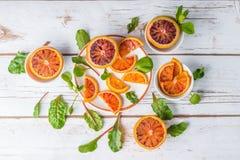 Naranjas de sangre con las hojas de la ensalada fotos de archivo