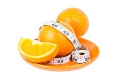 Naranjas en cinta de medición en la placa Imagen de archivo