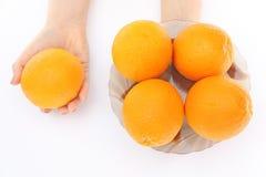 Naranjas en un cuenco a disposición Imágenes de archivo libres de regalías