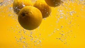 Naranjas enteras que caen en la cámara lenta del iin del agua metrajes