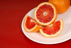 Naranjas enteras y del corte de sangre en la placa blanca imágenes de archivo libres de regalías