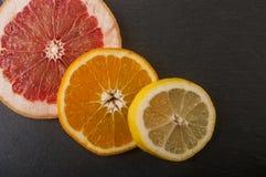 naranjas, pomelo, limón en un fondo negro Fotografía de archivo