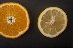 naranjas, pomelo, limón en un fondo negro Fotografía de archivo libre de regalías