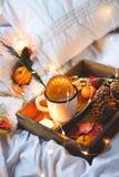 Naranjas secas del fondo de la Navidad, mandarinas dulces en una caja, café en una taza blanca foto de archivo