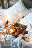 Naranjas secas del fondo de la Navidad, mandarinas dulces en una caja, café en una taza blanca imagenes de archivo