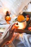 Naranjas secas del fondo de la Navidad, mandarinas dulces en una caja, café en una taza blanca fotos de archivo