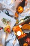 Naranjas secas del fondo de la Navidad, mandarinas dulces en una caja, café en una taza blanca fotos de archivo libres de regalías