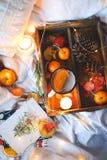Naranjas secas del fondo de la Navidad, mandarinas dulces en una caja, café en una taza blanca imagen de archivo libre de regalías