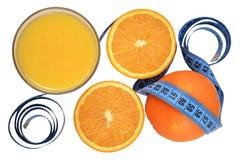 Naranjas, vidrio de zumo de naranja y cinta métrica Imagen de archivo