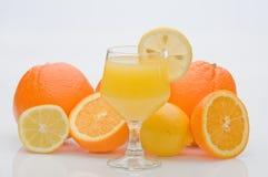 Naranjas y limones con el jugo de fruta. Imágenes de archivo libres de regalías