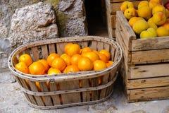 Naranjas y melocotones maduros en caja de madera y cesta en un mercado de la comida fotos de archivo libres de regalías