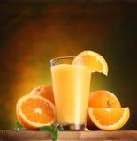 Naranjas y vidrio de jugo. Fotos de archivo
