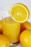 Naranjas y vidrio de zumo de naranja Foto de archivo libre de regalías
