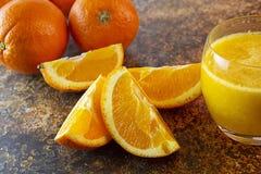Naranjas y zumo de naranja cortados en la tabla Fondo oscuro imágenes de archivo libres de regalías