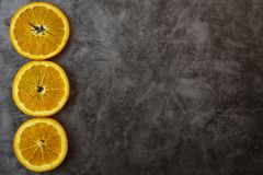 Naranjas y zumo de naranja cortados en la tabla Fondo oscuro imagen de archivo