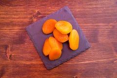 Narbige Aprikosen auf Schieferbehälter auf dem Holz gesehen von oben stockfotografie