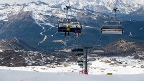 Narciarka i snowboarder używa narciarskiego dźwignięcie w popularnym ośrodku narciarskim obraz stock