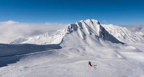 Narciarka samotnie na narciarskich skłonach z szczytami i błękitnym sk Obrazy Royalty Free
