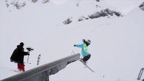 Narciarka skacze na żelaznym śladzie w śnieżnej górze stunts Konkursu wyzwanie ekstremum ski park zdjęcie wideo