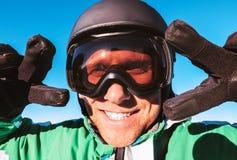 Narciarka ubierał w narciarskim hełmie i narciarscy gogle pokazuje dwa ` zwycięstwa ` gestykulują portret fotografia royalty free