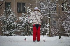Narciarka w mieście na tle dom zima sport - przez cały kraj narciarstwo śnieżny ślad dla narciarstwa żyć blisko lasu obraz stock