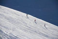 Narciarki iść w dół skłon przy ośrodkiem narciarskim. Obrazy Stock