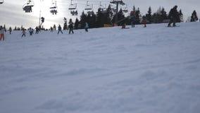Narciarki i snowboarders pochodzi na śnieżnym skłonie w górze Ludzie jedzie na narciarskim dźwignięciu przy wzgórzem Piękna zima zdjęcie wideo