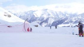 Narciarki i snowboarders przy ośrodkiem narciarskim, widokiem na zimy śnieżnych górach i narciarskim dźwignięciem, zbiory wideo